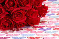 Artificial roses, over background of hearts, space for copy.