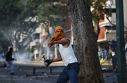 An anti-government protestor throws a bottle at members of the Venezuelan army  during the 5th straight day of clashes in Caracas.  The effort to hold a referendum against President Chavez took an expected step backwards when an Electoral Council said there are currently not enough valid signatures to request the referendum.