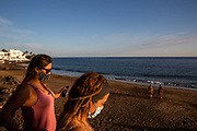 Two women wearing face masks walk onto a quiet beach at sunset in Puerto Del Carmen, Lanzarote, Spain on 21st November 2020. Beaches across the island are nearly deserted since tourism plummeted due to Covid restrictions elsewhere in Europe. Although the Canary Islands have been relatively unscathed by the virus, with 155 lives lost from 2.1 million residents, the region is heavily dependent on tourism and locals are hoping that numbers recover as lockdown measures and potentially vaccines reduce the number of infections in Europe.