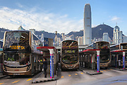 Bus station near the Star Ferry pier in Tsim Sha Tsui with the skyscraper of the International Finance Centre behind.  Hong Kong, China. Thursday January 11th 2018