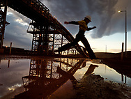 An iron ore worker jumps a puddle at a Pilbara ore processing plant after a rain storm.