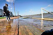 Nederland, Nijmegen, 12-3-2020 In Nijmegen en de aangrenzende Ooijpolder staat het water van de Waal verhoogd. De waalkade is vorig jaar voor een deel met 1 meter verlaagd, en overstrolmt daarom sneller als voorheen. Hij is afgesloten voor verkeer en de bussen nemen een alternatieve route.. Foto: Flip Franssen