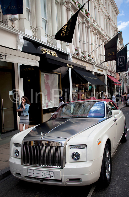 """Rolls Royce car parked outside Chanel Jewellers. Exclusive shops on New Bond Street, Mayfair, central London. It is one of the principal streets in the West End shopping district and is more upmarket. It has been a fashionable shopping street since the 18th century. Technically """"Bond Street"""" does not exist: The southern section is known as Old Bond Street, and the northern section, which is rather more than half the total length, is known as New Bond Street. The rich and wealthy shop here mostly for high end fashion and jewellery."""