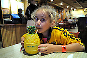 8 year old Australian child drinking from novelty container in restaurant. Waikiki, Honolulu, Hawaii