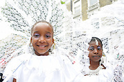 Two girls peer out from their lace shades during the Notting Hill Carnival 2007