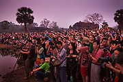 Tourists using digital devices - iphones, tablets, ipads, cameras -  photograph the dawn at Angkor Wat; waiting to see the light come up over the main temple of Angkor.<br /> Angkor is one of the most important archaeological sites in South-East Asia. Stretching over some 400 km2, including forested area, Angkor Archaeological Park contains the magnificent remains of the different capitals of the Khmer Empire, from the 9th to the 15th century. They include the famous Temple of Angkor Wat and, at Angkor Thom.  UNESCO has set up a wide-ranging programme to safeguard this symbolic site and its surroundings