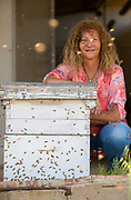 A female beekeeper is standing next to a beehive admiring a worker bee. Photographed in Haniel [a moshav in central Israel. Located in the Sharon plain near Netanya and Kfar Yona], Israel