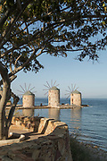 Calm blue sea with famous historical stone windmills at Tampakika, Chios, Greece