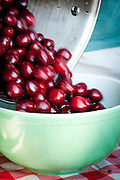 Fresh cherries being poured into a bowl