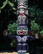 Grizzly Bear over man's head and Dzunukwa, the giantess, figures on the Ga'akstalas Pole, carved by Wayne Alfred and Beau Dick in 1991 and based on a Kwakwaka'wakw design by Russell Smith.  Totem pole on display at Stanley Park, Vancouver, British Columbia, Canada.