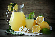 Jug and glass with lemon juice decorated with fresh lemons and mint leaves.