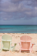 Pastel colored adirondack chairs on Love beach  in Nassau, Bahamas