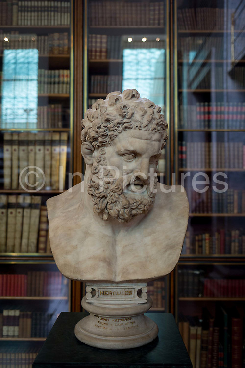 The bust of mythical Hercules, a Roman copy of the ancient Greek original by Lysippos of about 325-300BC in the Enlightenment Gallery of the British Museum on 28th February 2017, in London, England. The Roman version is said to have been found in lava at the foot of Vesuvius and presented to the museum by Sir William Hamilton in 1776. Hercules is the Roman adaptation of the Greek divine hero Heracles,  the son of Zeus Roman equivalent Jupiter and the mortal Alcmene. In classical mythology, Hercules is famous for his strength and for his numerous far-ranging adventures.
