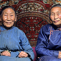 MONGOLIA, Elder sisters in a nomadic family pose in their best dels (robes) in their ger.  Bayar is on the right, Ayush on the left.