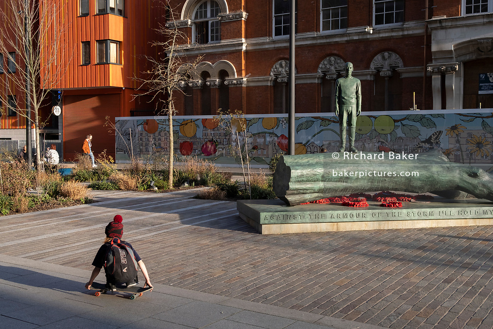 """The bronze sculpture of a boy forms part of the artwork by Kenny Hunter in Walworth Square at Elephant And Castle on 9th March 2021, in London, England. Its full inscription reads """"Against the armour of the storm I'll hold my human barrier"""" – a line from a World War Two poem by Hamish Henderson. The striking bronze artwork has been installed in the year that marks the centenary of the Armistice and the end of the First World War. The sculpture has been commissioned to commemorate all the lives that have been affected by war and conflict around the globe, including the lives of members of the armed forces, civilians, refugees and others."""