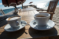 Two cups of coffee sit on a brown wooden slatted table on the beach at Juan-les-Pins on the French Riviera.<br /> Sand, the Mediterranean Sea, umbrellas and chairs are out-of-focus in the background.