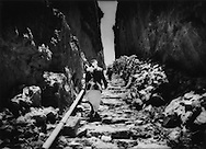 Yahya follows his son and the village water supply pipe through cleft in mountain that leads to the Kawkaban city gate.   Until the modern road was built, this one, easily defended, trail made Kawkaban impregnable, Sana'a Governate, Yemen.