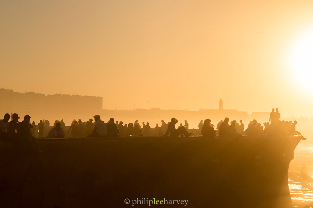 Silhouettes of tourists enjoying sea view at foggy sunset, Casablanca, Morocco