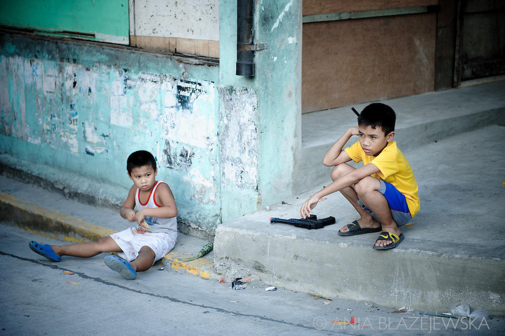 Philippines, Manila. Two filipino boys playing with a gun.