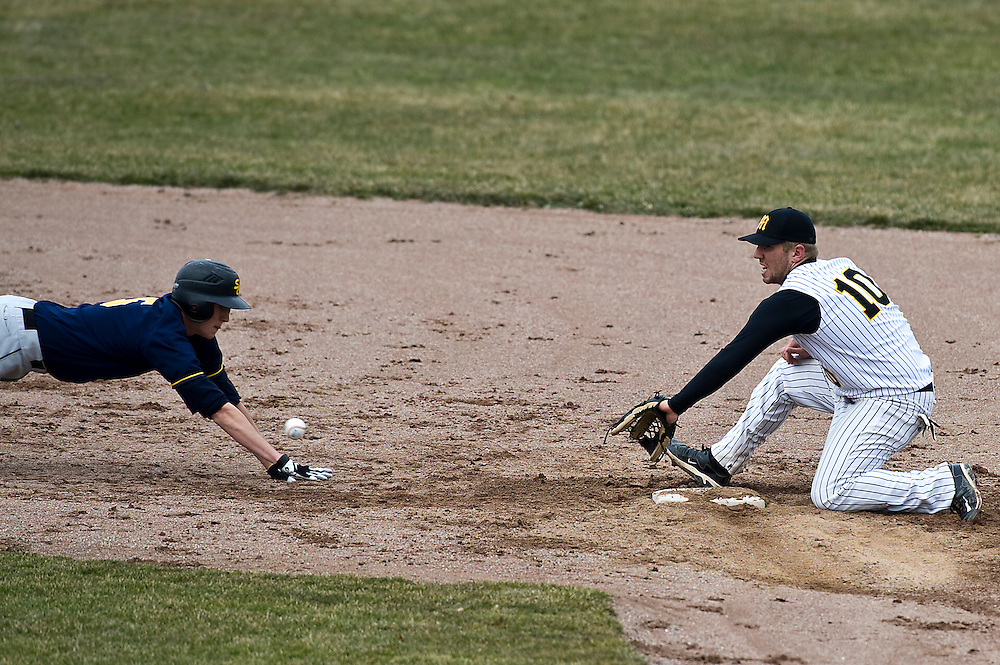 Matt Dixon | The Flint Journal..Mott's Shane Shroyer prepares to catch the ball as St. Clair's Kevin Fisher dives into second base in Mott's conference home-opener at Broome Park in Flint Friday afternoon.Mott defeated St. Clair 6 to 5 in the bottom of the eighth inning.