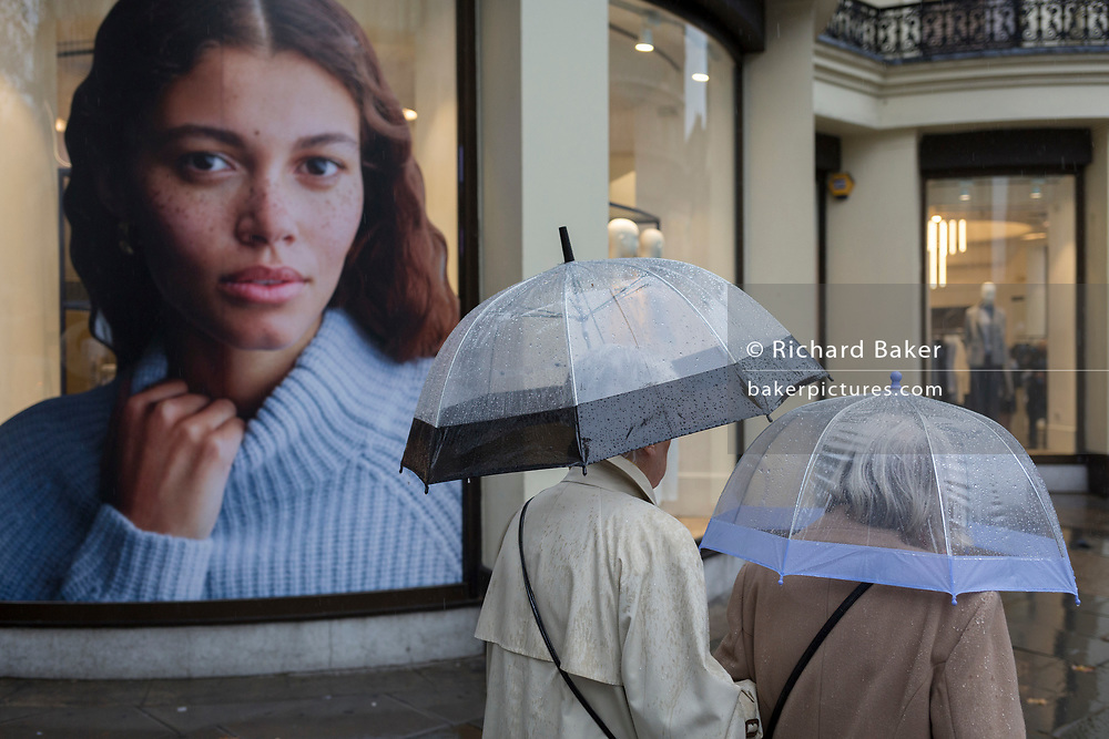 Two ladies use transparent umbrellas during heavy rainfall on an autumn afternoon on the Strand, on 24th October 2019, in Westminster, London, England.
