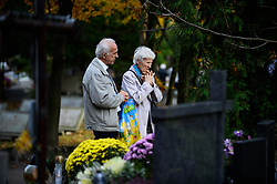 November 1, 2018 - Krakow, Poland - A couple seen praying next to a grave at  the Rakowicki Cemetery during the celebration..All Saints Day, also known as The Day of the Dead, is a Roman Catholic day of remembrance for friends and loved ones who have passed away. (Credit Image: © Omar Marques/SOPA Images via ZUMA Wire)