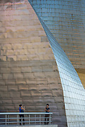 Couple taking photographs at Architect Frank Gehry's Guggenheim Museum at Bilbao, Basque country, Spain