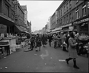 Moore Street, Dublin.      (J97)..1975..23.12.1975..12.23.1975..23rd December 1975..For well over a hundred years Moore Street has served the citizens of Dublin. The longest running open air fruit and vegatable market offers value for money,particularly to those where money is in short supply. Predominately a fruit and veg market there are several traders who sell fish and seasonal goods, as illustrated by the photographs showing turkeys and holly wreaths being sold on the run up to Christmas..A view down Moore Street from Henry Street