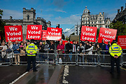Brexit protesters hold placards as judges walk to the Palace of Westminster following the annual Judges Service which marks the start of the new legal year at Westminster Abbey in London, United Kingdom on 1st October 2019.