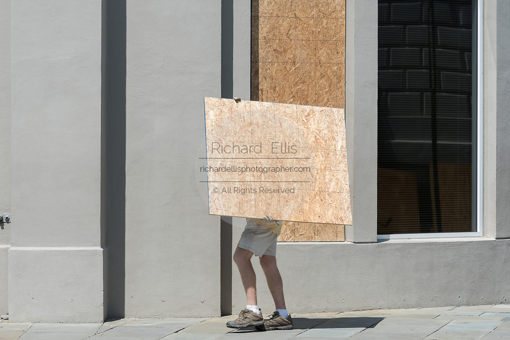 A worker carries plywood to secure windows on historic Broad Street in preparation for Hurricane Irma September 8, 2017 in Charleston, South Carolina. Imra is expected to spare the Charleston area but hurricane preparations continue as Irma leaves a path of destruction across the Caribbean.