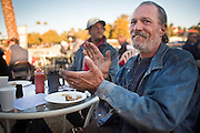 "Jan 10, 2010 - PHOENIX, AZ: RALPH, a homeless man in Phoenix, applauds after morning prayers during breakfast at CrossRoads United Methodist Church in Phoenix, AZ. The church has been ordered by city zoning officials to stop serving breakfast to the homeless and indigent on Saturday mornings. The church started serving breakfast to the homeless in Jan. 2009 and shortly after that neighbors in the upscale area of Phoenix complained to city officials that the church was in violation of zoning ordinances. The city found the church was operating a ""charity kitchen"" and ordered them to stop serving the breakfast. Rev. Dottie Escobedo-Frank, the pastor of the church, has said the church will file an appeal in US District Court and continue serving the breakfast until the appeals process is exhausted. About 150 people attend the Saturday breakfast each week. Some walk to the church from the alleys they live in in the neighborhood, others are bused to the breakfast by the church, which sens a bus in 1.5 mile radius from the church.         Photo by Jack Kurtz"