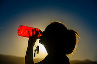 A young woman drinking water from a Nalgene bottle, Littleton, Colorado USA.