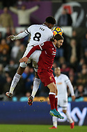 Adam Lallana of Liverpool jumps for a header with Leroy Fer of Swansea city (8). Premier league match, Swansea city v Liverpool at the Liberty Stadium in Swansea, South Wales on Monday 22nd January 2018. <br /> pic by  Andrew Orchard, Andrew Orchard sports photography.