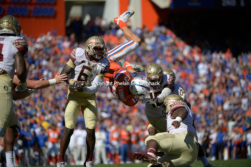 Florida quarterback Feleipe Franks (13) is upended by Florida State linebacker Matthew Thomas (6) and linebacker Ro'Derrick Hoskins (18) on a quarterback keeper during the first half of an NCAA college football game Saturday, Nov. 25, 2017, in Gainesville, Fla. (Photo by Phelan M. Ebenhack)