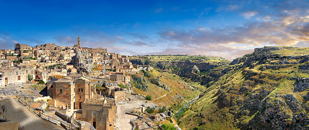 """Panoramic ew of """"la Gravina"""" ravine and the Sassi of Matera, Basilicata, Italy. A UNESCO World Heritage site.<br /> <br /> The area of Matera has been occupied since the Palaeolithic (10th millennium BC) making it one of the oldest continually inhabited settlements in the world. <br /> The town of Matera was founded by the Roman Lucius Caecilius Metellus in 251 BC and remained a Roman town until  was conquered by the Lombards In AD 664 becoming part of the Duchy of Benevento.  Matera was subject to the power struggles of southern Italy coming under the rule of the Byzantine Roman, the Germans and finally Matera was ruled by the Normans from 1043 until the Aragonese took possession in the 15th century. <br /> <br /> At the ancient heart of Matera are cave dwellings known as Sassi. As the fortunes of Matera failed the sassy became slum dwelling and the appalling living conditions became be the disgrace of Italy. From the 1970's families were forcibly removed from the Sassi and rehoused in the new town of Matera. Today tourism has regenerated Matera and the sassi have been modernised and are lived in again making them probably the longest inhabited houses in the world dating back 9000 years. .<br /> <br /> Visit our ROMAN ART & HISTORIC SITES PHOTO COLLECTIONS for more photos to download or buy as wall art prints https://funkystock.photoshelter.com/gallery-collection/The-Romans-Art-Artefacts-Antiquities-Historic-Sites-Pictures-Images/C0000r2uLJJo9_s0<br /> .<br /> <br /> Visit our MEDIEVAL PHOTO COLLECTIONS for more   photos  to download or buy as prints https://funkystock.photoshelter.com/gallery-collection/Medieval-Middle-Ages-Historic-Places-Arcaeological-Sites-Pictures-Images-of/C0000B5ZA54_WD0s"""