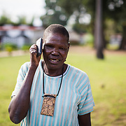 """""""The Bull"""" can barely hold his mobile phone due to the damage done to his fingers by Leprosy. Ifakara, Tanzania"""