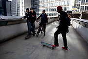 Urban youths hanging around with skateboards on a walkway in Waterloo, London, UK.This area near to the Southbank is a popular gathering point for young kids who subscribe to street culture.