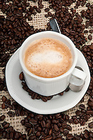 Cup of cappuccino coffee with background of coffee beans and burlap.