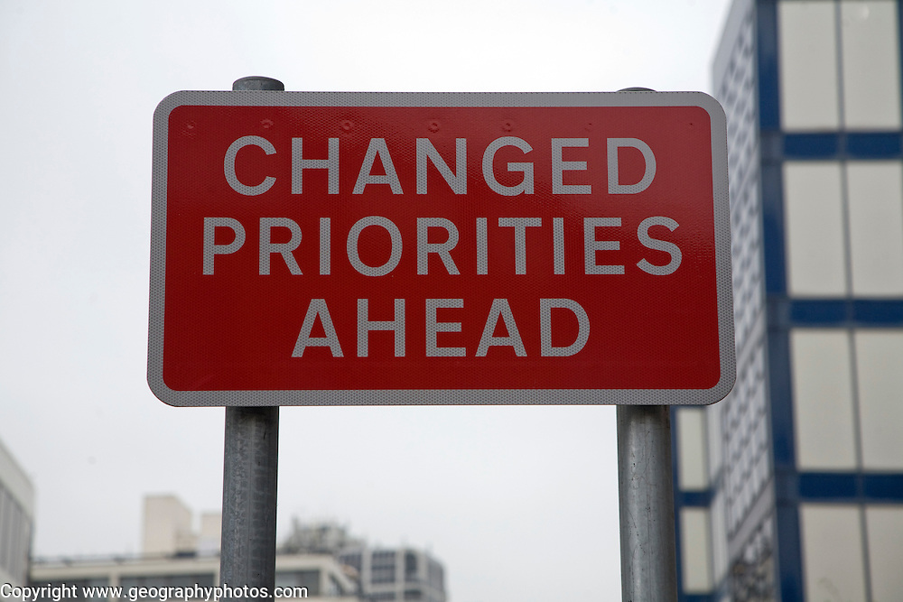 Road sign saying Changed Priorities Ahead on red background, UK