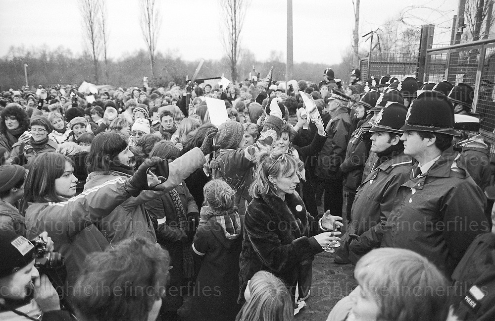 Women protestors taunt policeman as they stand guard around the perimeter fence of the Greenham Common Air Base in Berkshire where they were protesting against nuclear weapons being based at Greenham. November 1982.Photo by Jayne Fincher