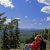 A mother and son relax with a scenic view of the Absaroka-Beartooth Mountains in Shoshone National Forest, Wyoming.