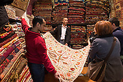 Salesman with traditional Turkish carpet rug in The Grand Bazaar, Kapalicarsi, great market, Beyazi, Istanbul, Turkey