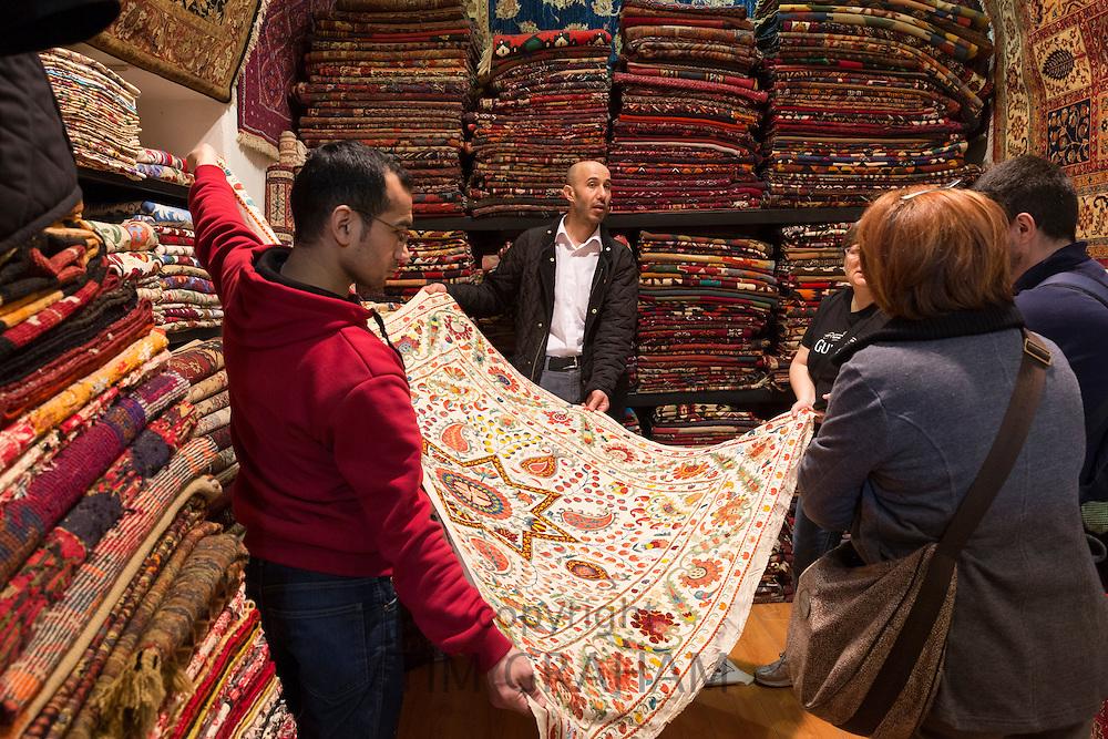 Salesman with traditional Turkish carpet rug in The Grand Bazaar, Kapalicarsi, great market, Beyazi, Istanbul, Turkey