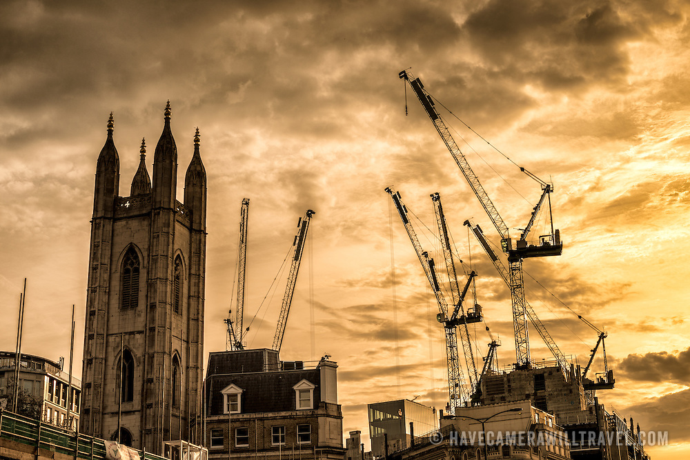 Silhouette of some of the construction cranes on London's skyline alongside some of the historic buildings.