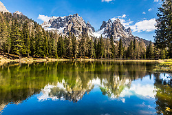 The jagged limestone peaks of the Dolomite Mountains reflection in the calm waters of Lago d'Antorno,  in Misurina, Italy.  Misurina is the next valley east or its more famous neighbor Cortina.