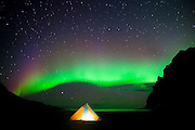 The aurora borealis appears above a glowing tent on Bunes Beach, Moskenesoya, Lofoten Islands, Norway.
