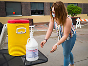 23 MAY 2020 - AMES, IOWA: CLAIRE OKOREN, a 2020 graduate of Iowa State University, washes her hands at the handwashing station at the entrance to the downtown Farmers' Market in Ames. The Ames Main Street Farmers' Market reopened Saturday after nearly a month of only online sales because of Iowa's bans on large gatherings caused by the COVID-19 pandemic. Only about 15 venders set up stalls Saturday and attendance was significantly lower than normal. All of the venders wore face masks and many, but not all, of the shoppers wore face masks. Farmers' markets are popular community gatherings in Iowa, but they've been on hiatus since the Coronavirus (SARS-CoV-2) pandemic. At this time, Iowa farmers' markets are not allowed to have entertainment or sell non-food or non-agricultural goods.          PHOTO BY JACK KURTZ