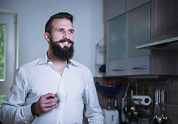 Young man drinking coffee in the kitchen and smiling, Bavaria, Germany