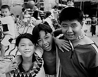 Three young Vietnamese boys near their beachside home in Nha Trang smiling, laughing and playing together.