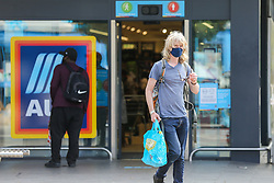 © Licensed to London News Pictures. 20/07/2021. London. UK. A shopper wearing a face covering leaves Aldi supermarket in Tottenham, north London on the day after Freedom Day. Face coverings are no longer a legal requirement, but the government expects and has recommended that people should continue to wear face coverings whilst shopping and in crowded areas, such as public transport. Photo credit: Dinendra Haria/LNP